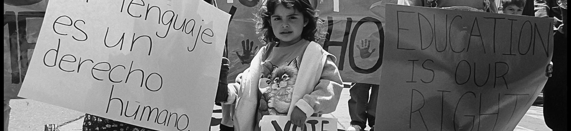 "black-and-white photo of children protesting prop 227 ""Language is a human right"" sign"